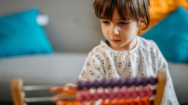 Une petite fille joue avec un jouet.