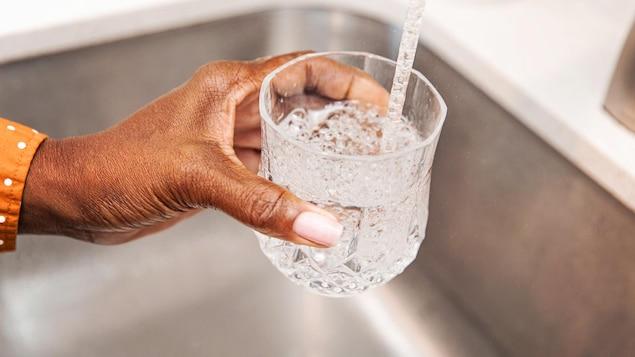 Une personne se sert un verre d'eau directement du robinet.