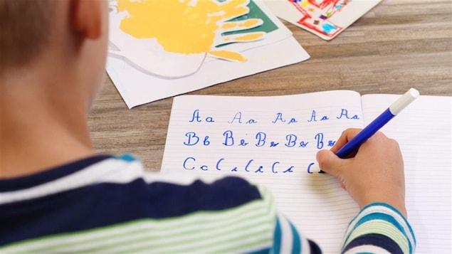 Un enfant écrit en lettres cursives dans un cahier.