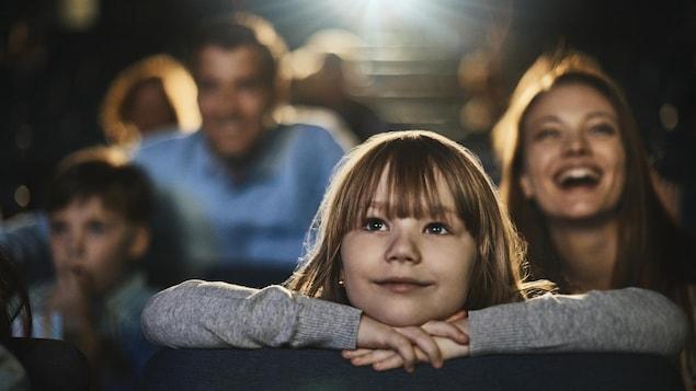 Une fillette appuie son menton sur ses mains, qui sont posées sur le dossier du siège devant elle, et regarde un film au cinéma avec un sourire.