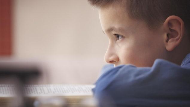 Un enfant prend une pause de lecture et regard devant lui.