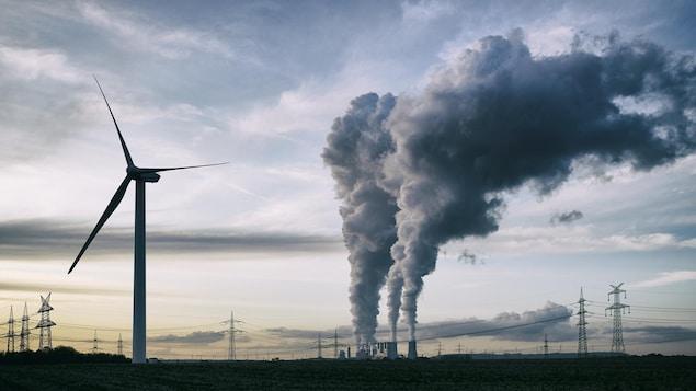 Une éolienne se dresse alors que des cheminées d'une centrale nucléaire crachent leur fumée au loin.