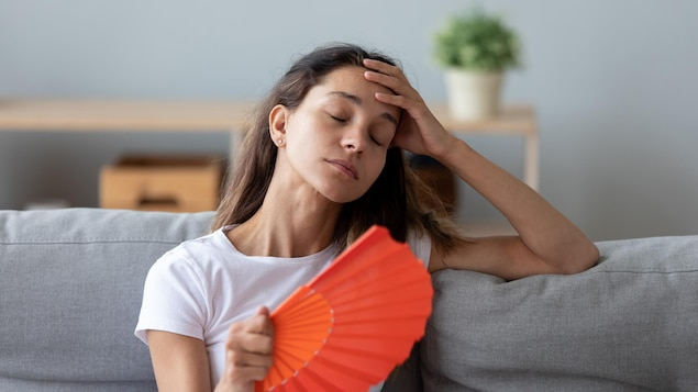 Une jeune femme, éventail à la main, souffre de la chaleur accablante.