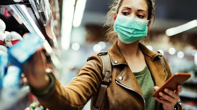 Une femme portant un masque prend un produit dans sa main droite pendant qu'elle se trouve dans un commerce.