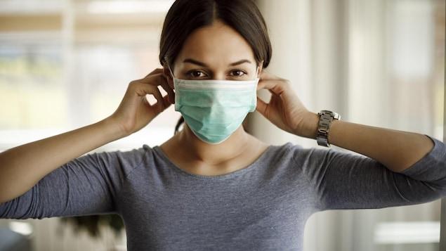 Une femme porte une masque pour se protéger de la COVID-19.