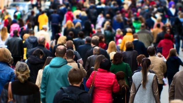 De nombreuses personnes marchent dans la même direction dans une rue.