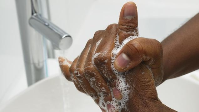Une personne se lavent les mains.