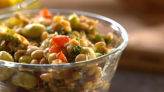 Une salade de légumineuses présenté sur une table dans un bol.