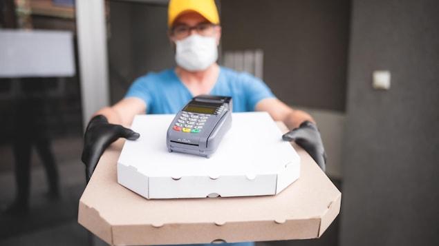 Une personne protégée par un masque et des gants livre deux pizzas à une autre personne.
