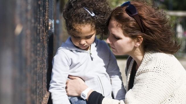 Une mère est à genou proche de sa petite fille qui regarde le sol.