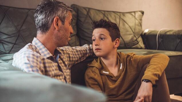Un père parle à son fils dans le salon.