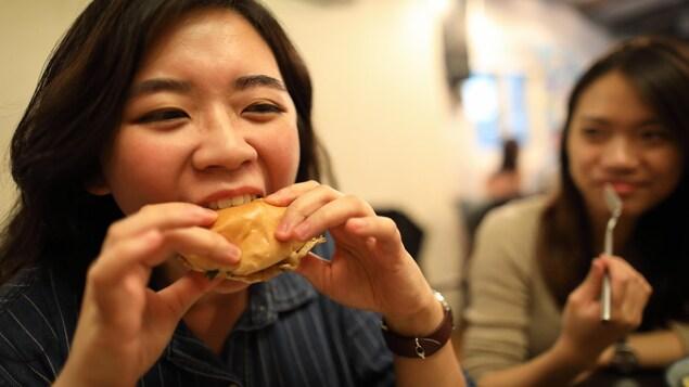 Une personne mange avec appétit de la nourriture dans un restaurant.
