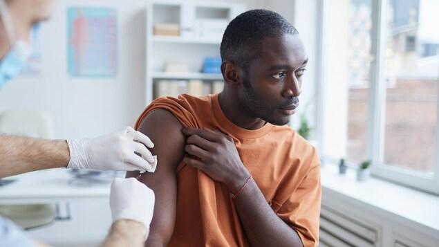 Une personne se fait vacciner sur le bras droit.