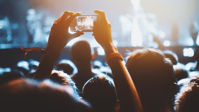 Une personne prend une photo pendant un concert.