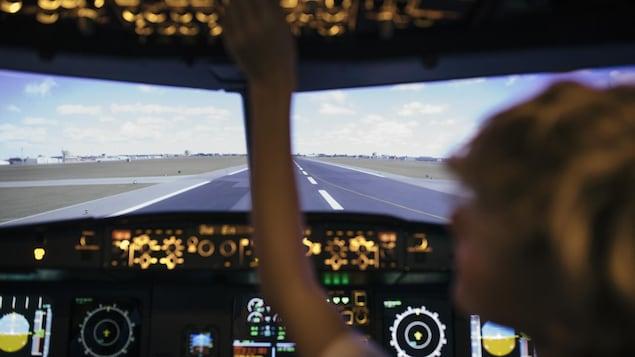 Une femme se trouve dans la cabine de pilotage d'un avion.