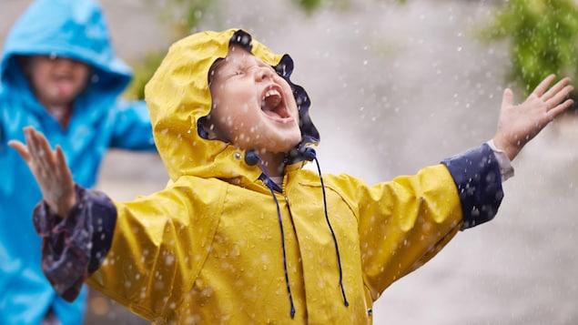 Un garçon ouvre la bouche pendant qu'il pleut.