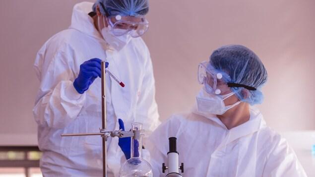 Des scientifiques masqués font des tests en laboratoire.