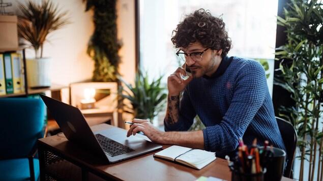 Un homme, téléphone cellulaire à la main, travaille de la maison devant son ordinateur.