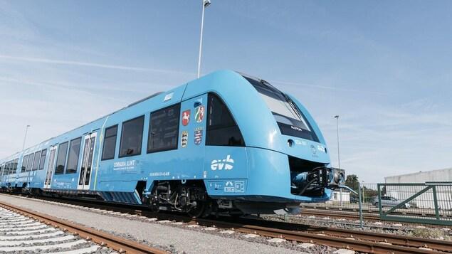Une voiture de train sur ses rails, dans une arrière-gare.