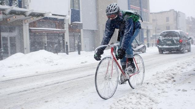 Une personne circule à vélo dans une rue enneigée de Montréal.
