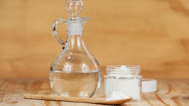 Une bouteille de vinaigre et un petit contenant de bicarbonate de soude sont déposés sur une table.