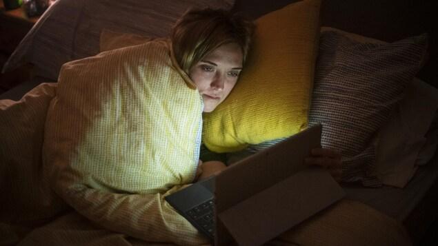 Une femme dans son lit, les lumières éteintes, regarde quelque chose sur son ordinateur.