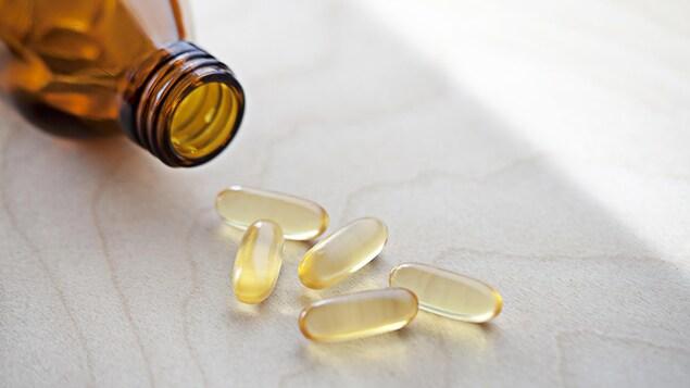 Des capsules de vitamine D sont déposées sur une table.