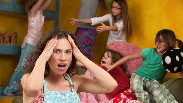 Une femme qui se prend la tête devant des enfants turbulents.