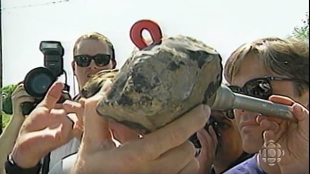 Une main montre aux journalistes la météorite qui est tombée à Saint-Robert, près de Sorel, le 14 juin 1994.