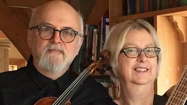 Un homme d'une soixantaine d'années avec des lunettes rondes avec un violon et une femme aux cheveux courts blonds.
