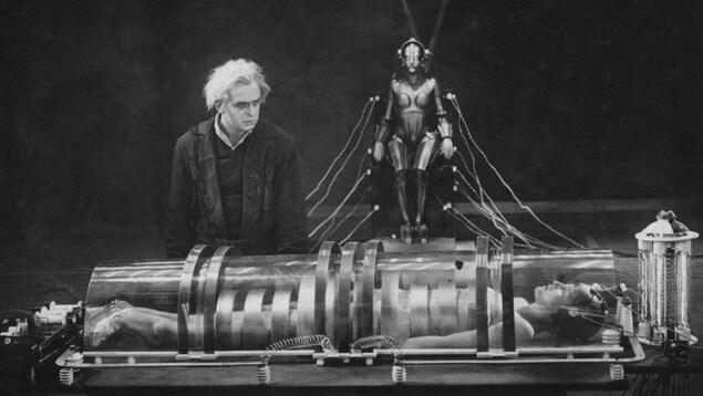 Scène du film Metropolis de Fritz Lang illustrant un homme devant le corps allongé d'une personne dans un grand tube de verre