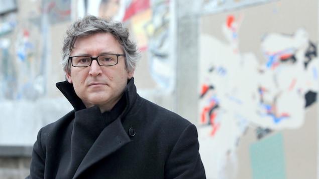 Assis vêtu d'un manteau noir, il porte des lunettes noires et des cheveux grisonnants.