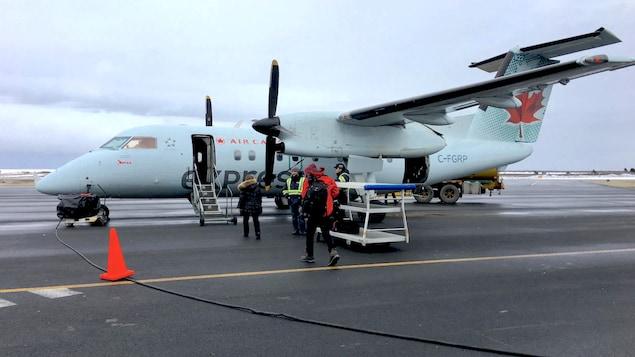 Des passagers qui embarquent dans un avion à l'aéroport des Îles-de-la-Madeleine.