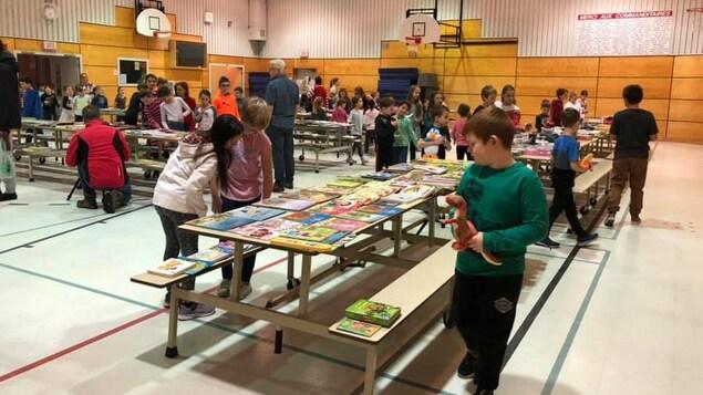 Des enfants accompagnés d'adultes à une kermesse de livres et jouets dans un gymnase scolaire.