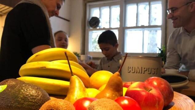 Une famille de deux adultes et deux enfants avec en avant plan des fruits posés sur une table.