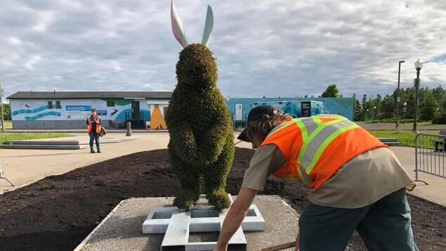 Un horticulteur devant une sculpture végétale représentant un lapin géant