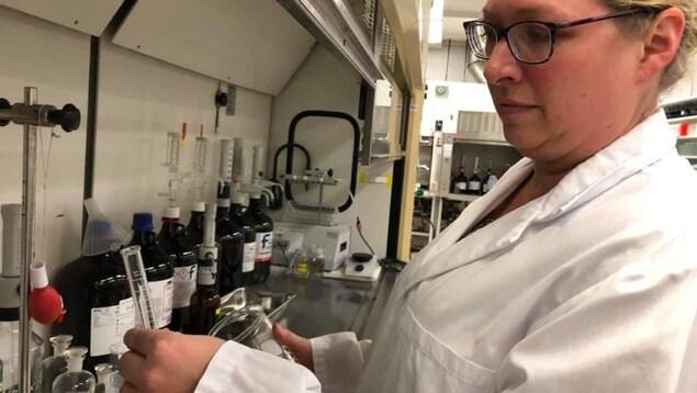 Dans un laboratoire d'analyses alimentaires, une femme en sarrau manipule une éprouvette