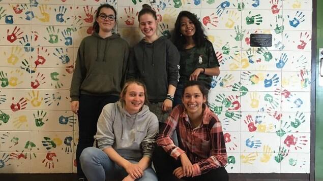 Cinq étudiantes posent devant le mur de la classe
