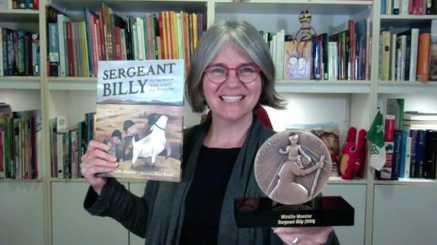 Mireille Messier sourit en tennant son livre sergent Billy dans une main et un prix dans l'autre.