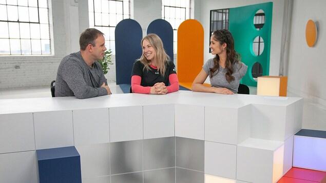 Un homme et deux femmes sont sur un plateau de télévision.