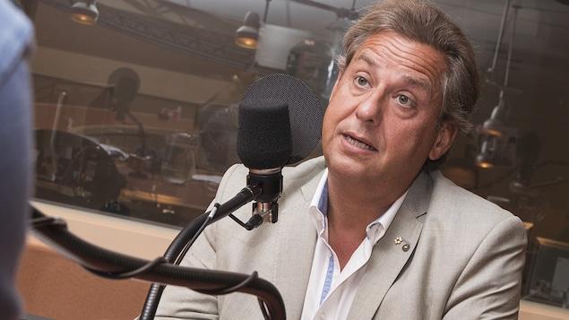 Alain Lefèvre devant un micro dans un studio de radio.