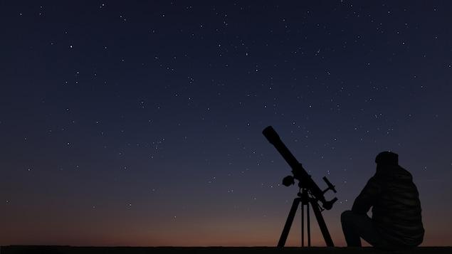 Un homme contemple le ciel étoilé.