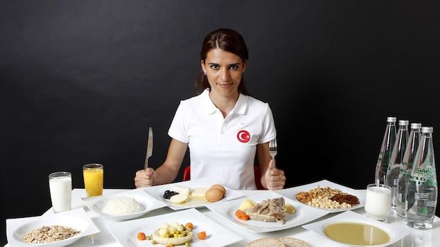 La coureuse turque Merve Aydin assise à une table présentant son alimentation typique d'une journée