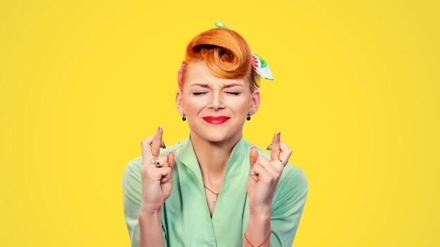 Une femme à l'allure rétro, sur fond jaune, se croise les doigts en fermant les yeux.