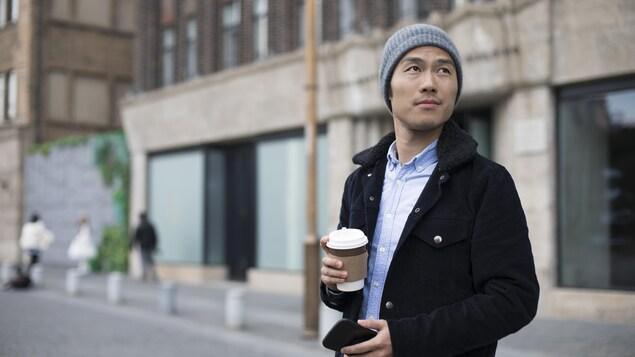 Un jeune homme marche dans la rue avec un café pour emporter dans la main.