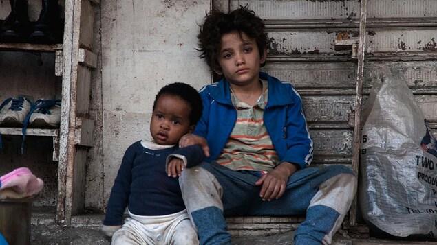 Boluwatife Treasure Bankole et Zain Al Rafeea regardent au loin, assis sur le sol contre un mur, dans cette image tirée du film <i>Capharnaüm</i>, de Nadine Labaki.