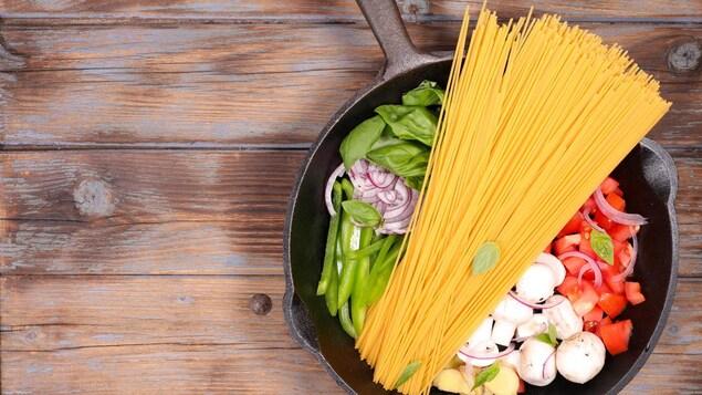 Des légumes et des pâtes séchées au fond d'une casserole, sur un comptoir en bois.