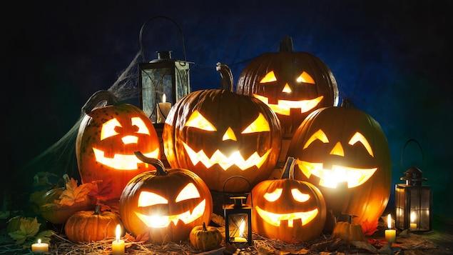 Des citrouilles décorées pour l'Halloween reposent les unes sur les autres.