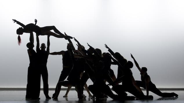Silhouettes de danseurs effectuant une chorégraphie sur fond blanc.