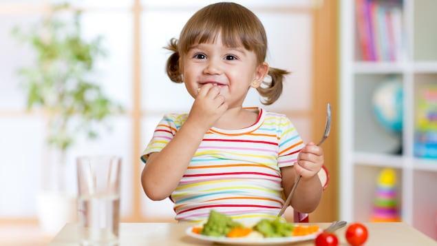 Une fillette mange des légumes avec le sourire.